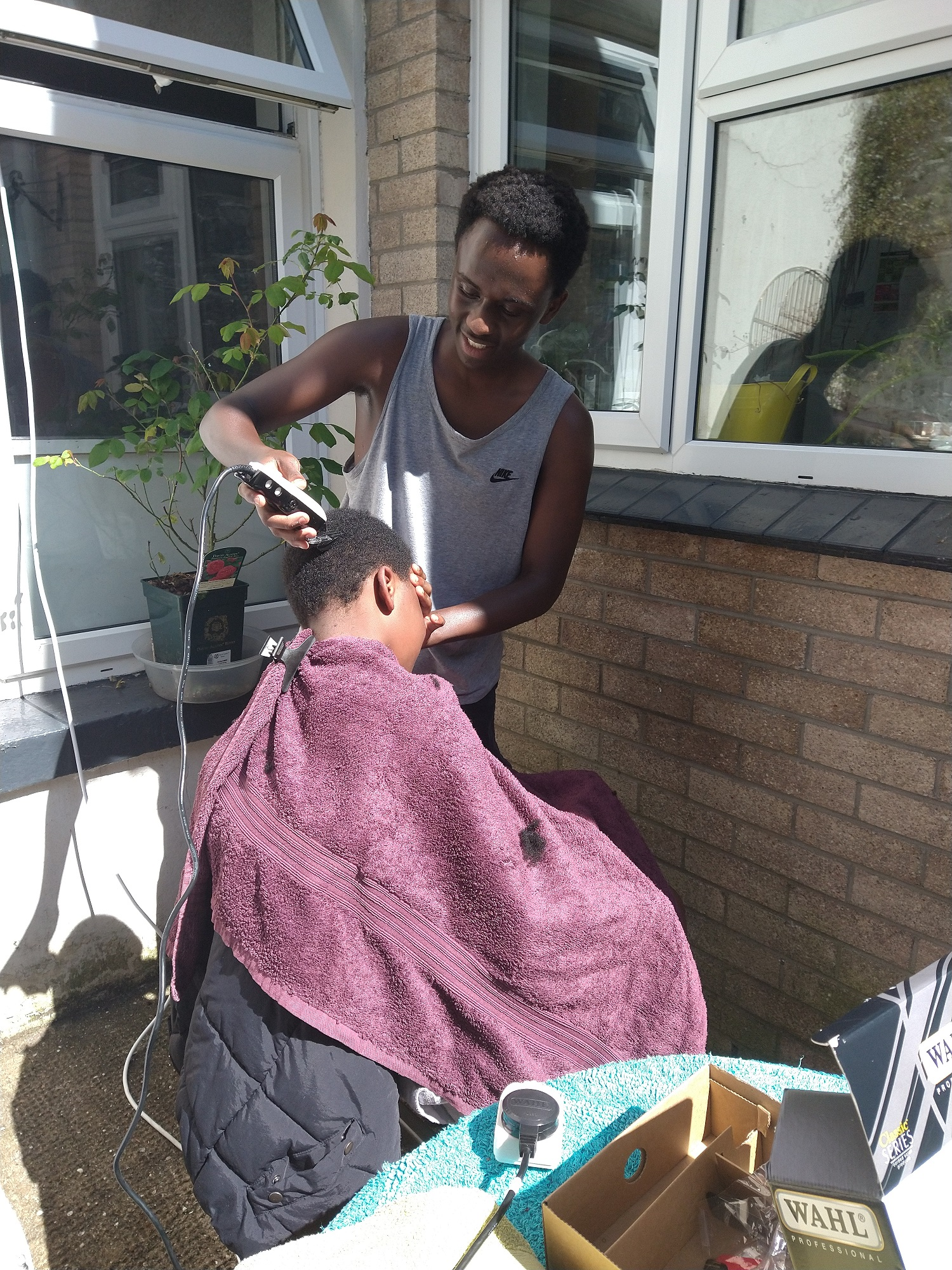 A male cuts the hair of a younger male outside