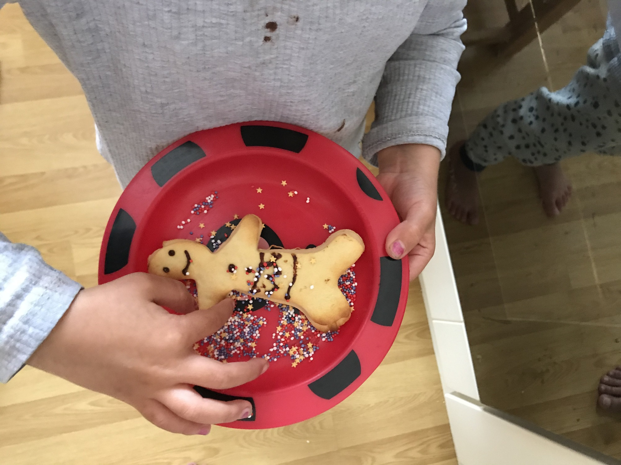 A small child holds a plate with a cookie shaped like a human on
