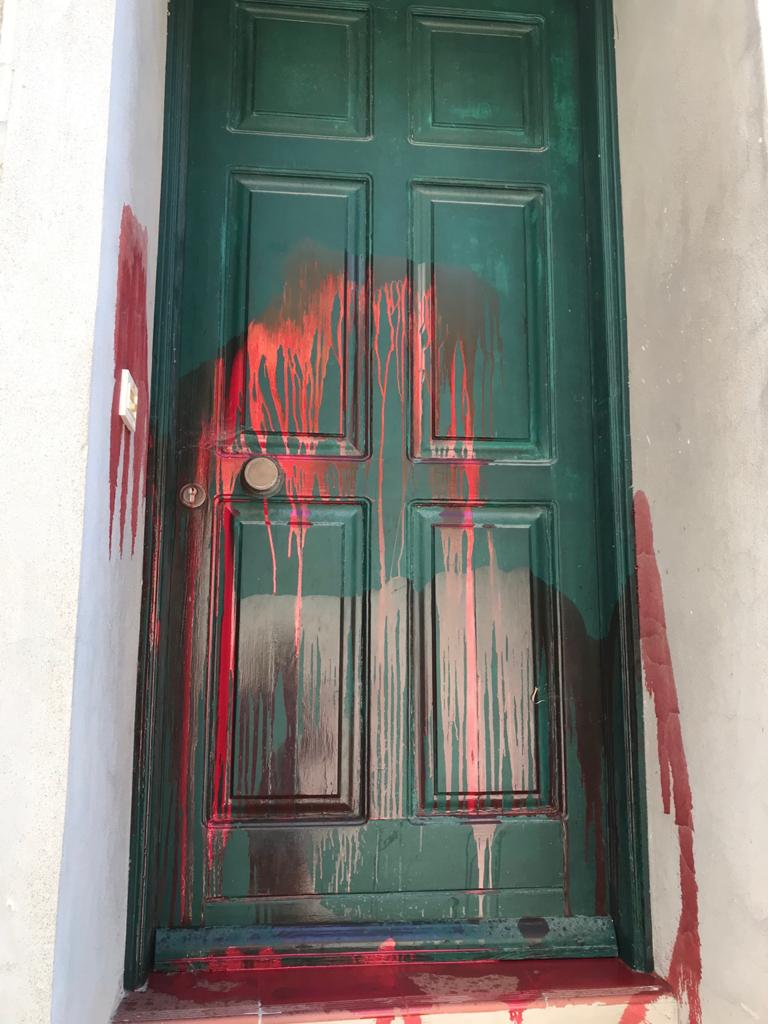 Red paint is splattered across a green front door on Lesvos
