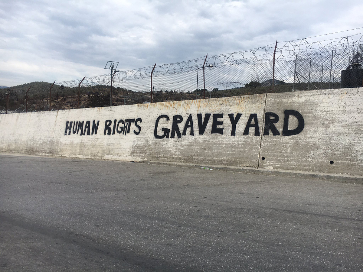 Grafitti on a large wall reads Human Rights Graveyard