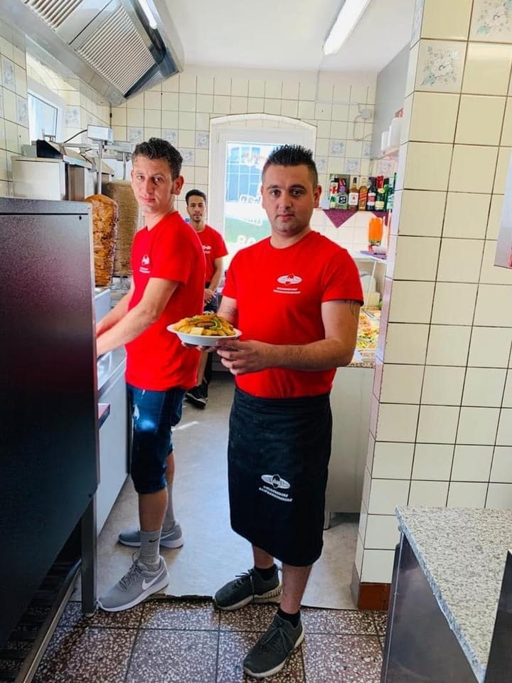 Two men stand in a catering establishment in red shirts