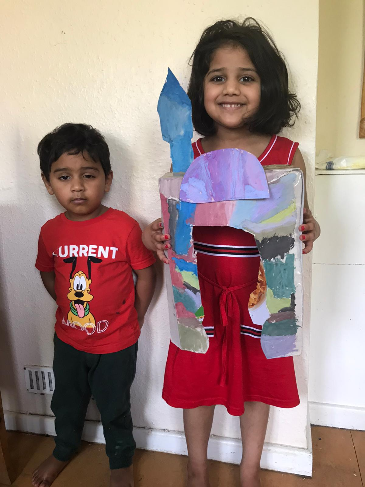 Two beautiful, happy children showing off their work, one boy and one girl