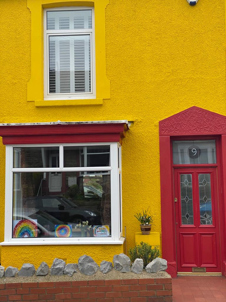 A colourful yellow house with a red door in South Wales supporting the NHS and care workers.