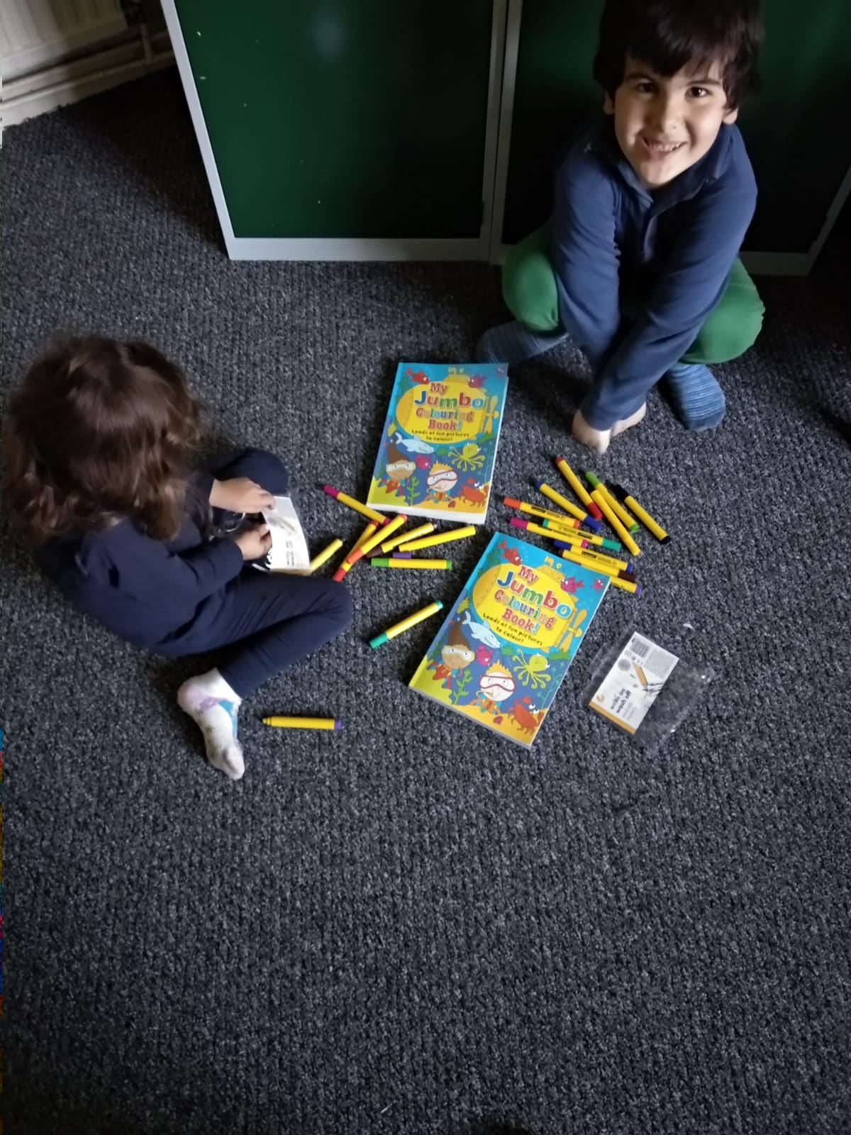 Two happy children colouring while sitting on the floor