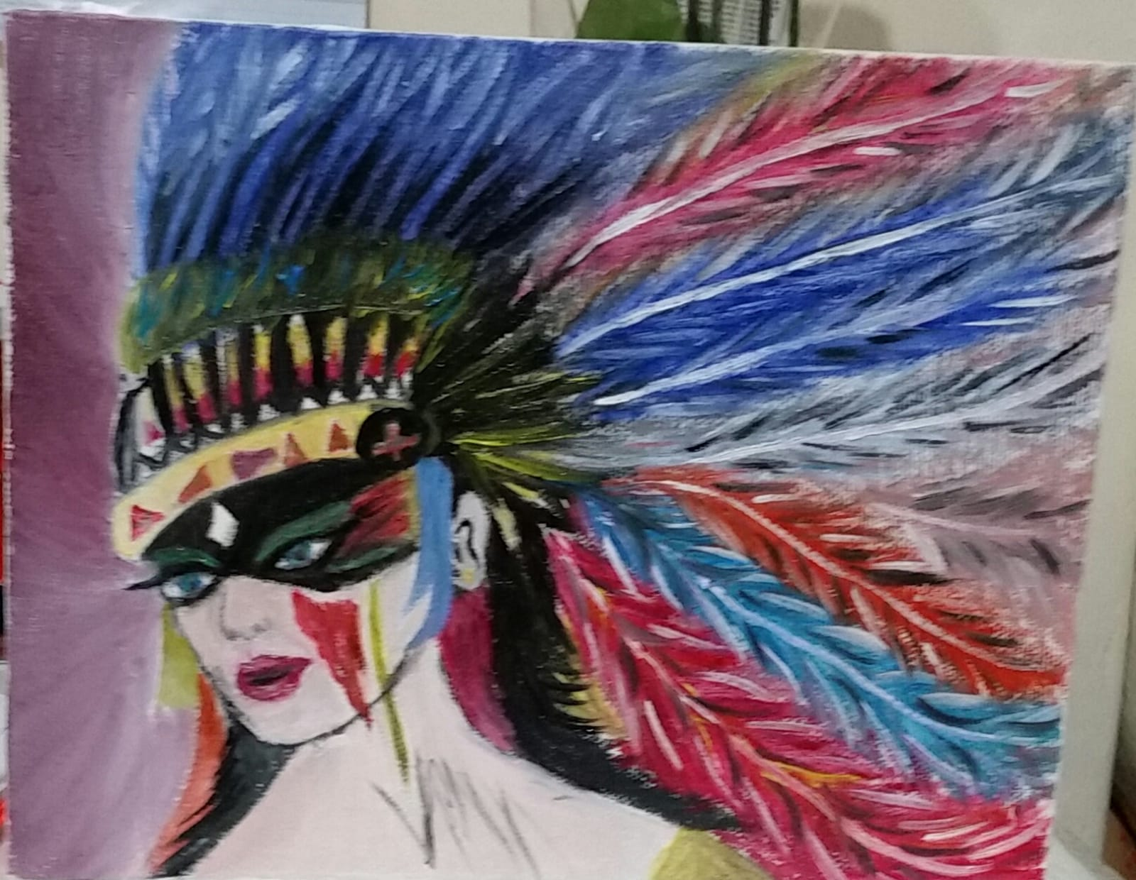A colourful head dress is worn by a woman, it has feathers coming from it
