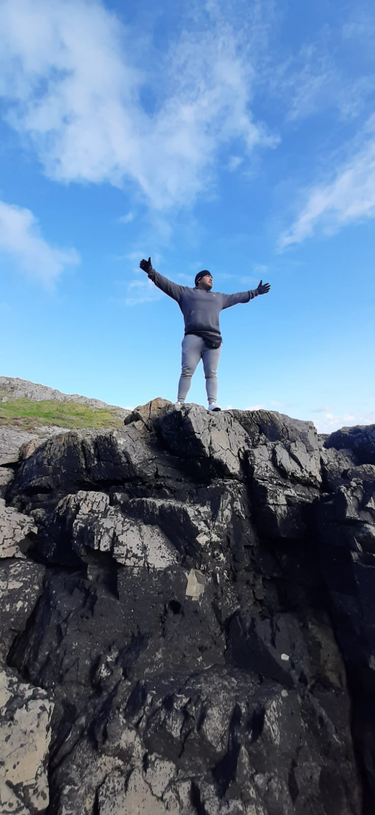 Armando stands on a high rock with his arms stretched wide with the blue expanse of the sky behind him