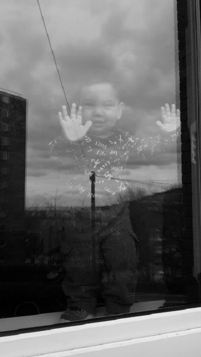 A gorgeous, happy toddler stands with his hands pressed up against a window smiling at the photographer