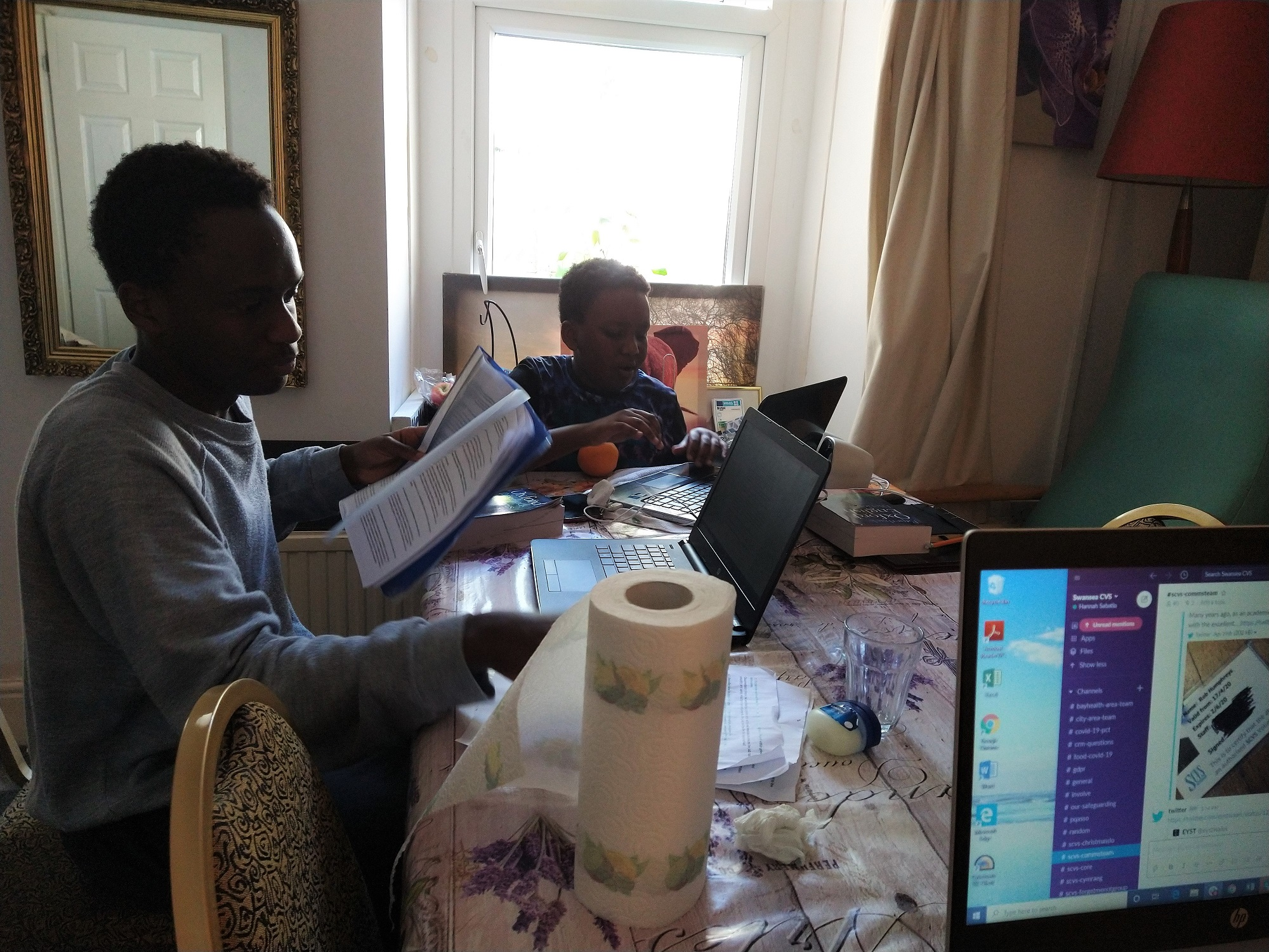 A man and child work together at a dining table, filled with technology and papers as they work from home
